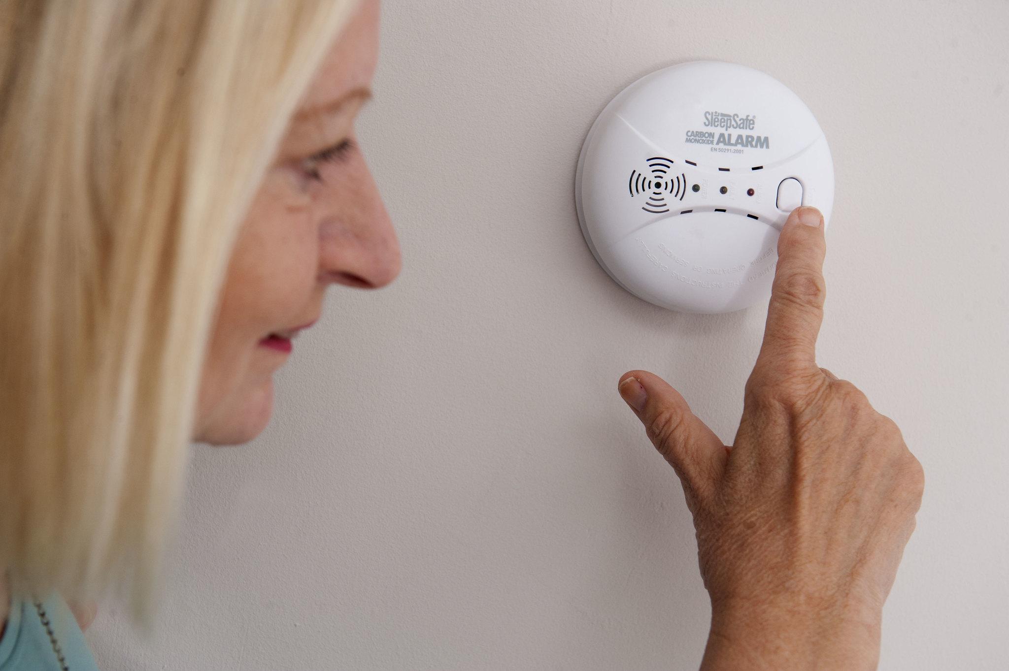Lady checking a carbon monoxide alarm